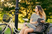 Porträt einer attraktiven Brünette sitzt auf einer Bank mit Fahrrad
