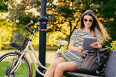 Photo Portrait of an attractive brunette sits on a bench with bicycle