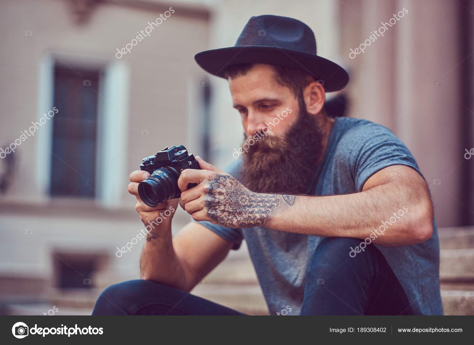 Hombre guapo hipster con una elegante barba y tatuajes en los brazos  vestido con ropa casual y sombrero tiene una cámara b9b457a12fb