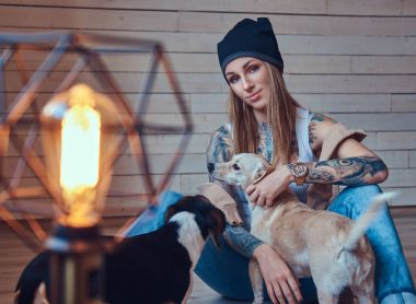 A stylish tattooed blonde female in t-shirt and jeans with her dogs