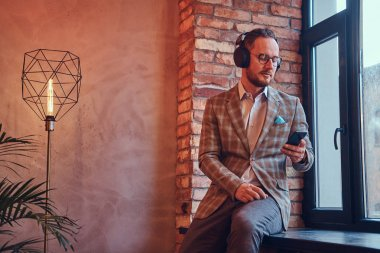 Portrait of a stylish man in a flannel suit and glasses listening music with the phone and headphones sitting on a window sill in a room with loft interior.