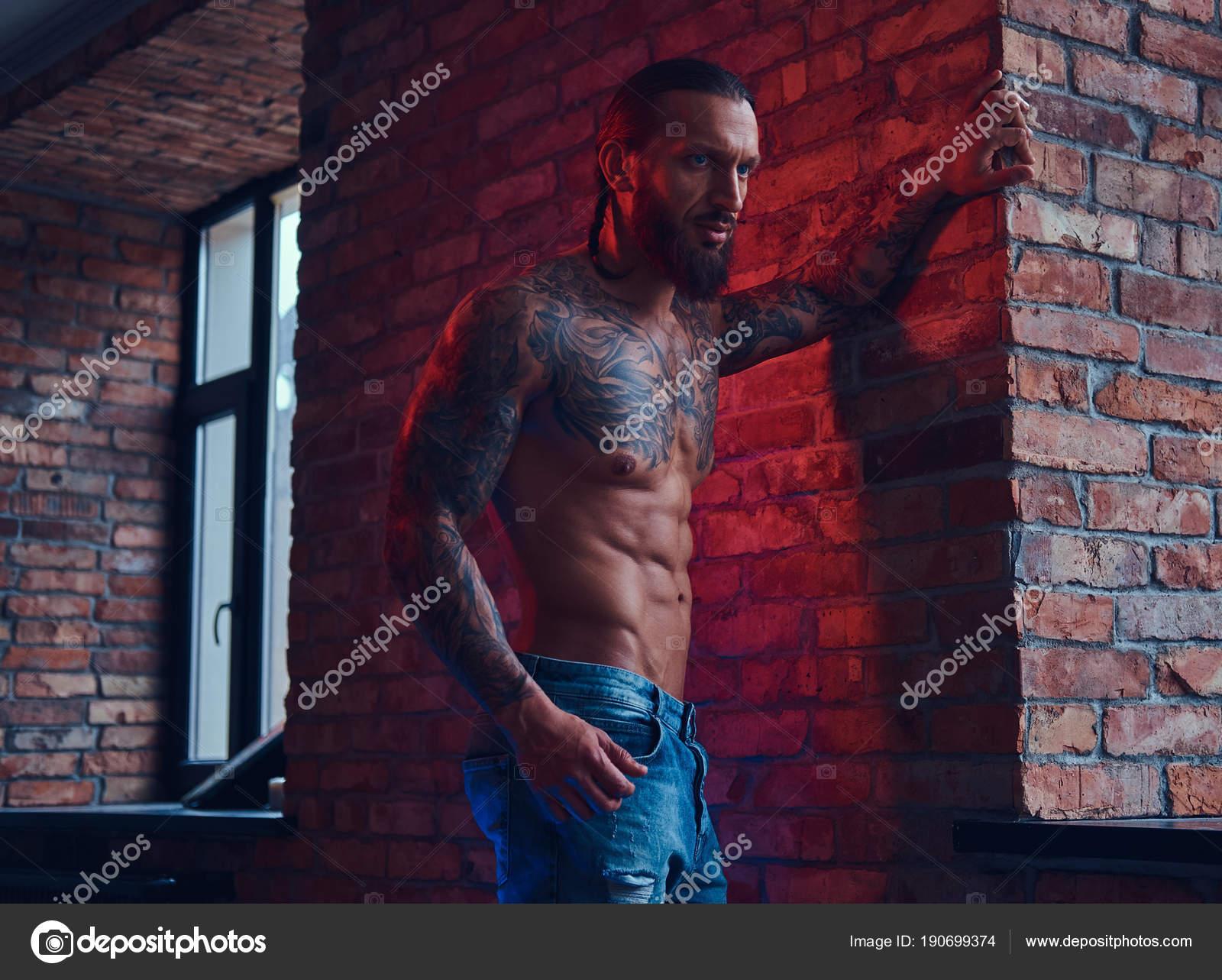 Ein hübscher tätowierten nacktem Oberkörper Mann mit eine stilvolle ...