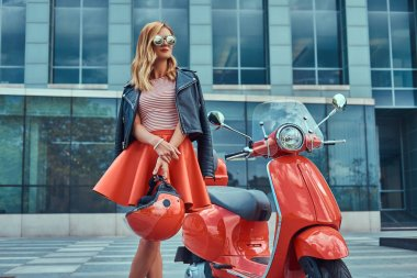 A sexy stylish blonde girl wearing a red skirt and black leather jacket and sunglasses, holding a helmet and standing near classic Italian scooter against a skyscraper.