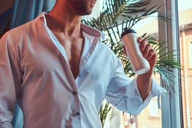Close-up portrait of a tall bearded male with a muscular body, dressed in a white shirt, drink protein before a morning workout.