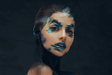 A young sensual girl with creative make-up. Blue and black shadows painted on her face. Conceptual idea.