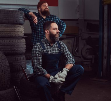 Two bearded mechanics near a stack of old car tires in the garage.