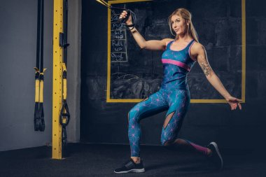 Beautiful muscular blonde woman in sportswear with a tattoo on her arm doing exercise with TRX system at gym. TRX concept.