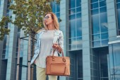 Photo Beautiful fashionable woman in stylish clothes and glasses with a handbag, standing against a skyscraper.