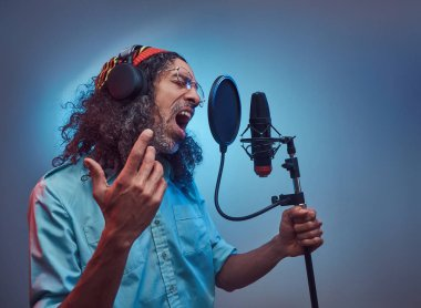 African Rastafarian singer male wearing a blue shirt and beanie emotionally writing song in the recording studio.