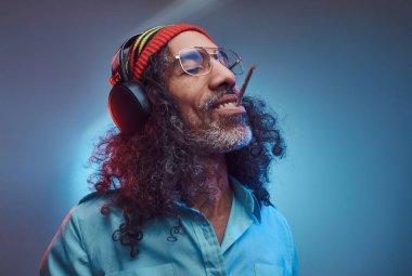 Studio portrait of African Rastafarian male enjoys music in headphones and smoking weed.