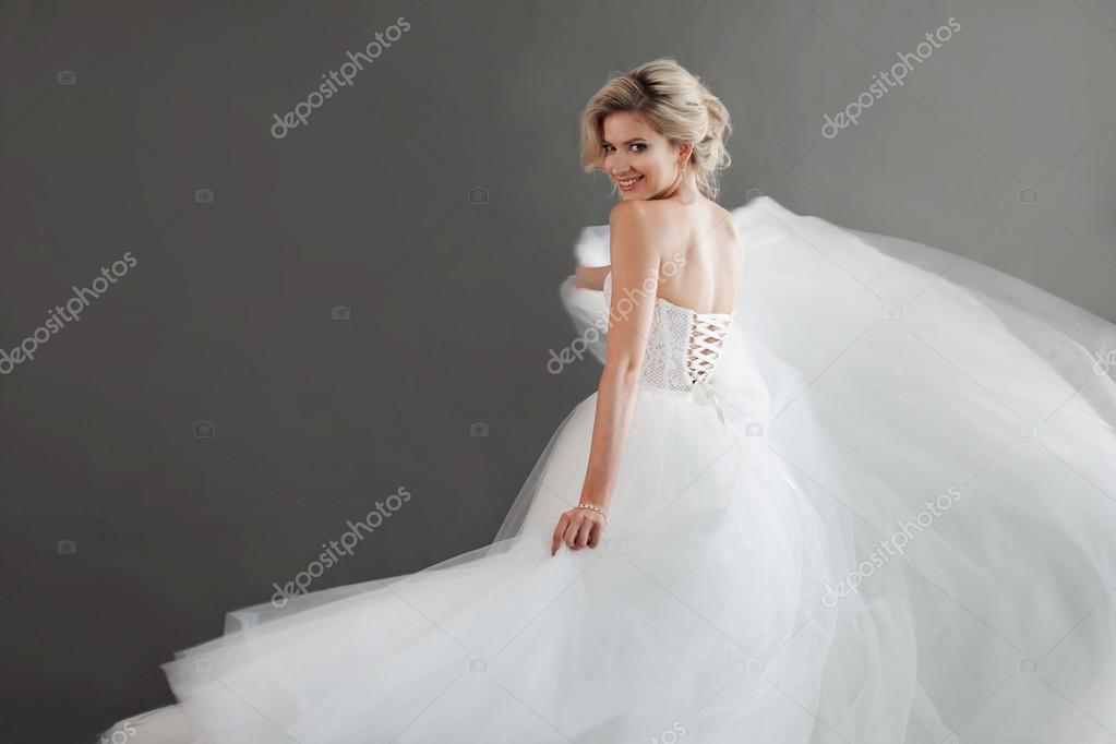 Tanzende junge Braut im luxuriösen Hochzeitskleid. Hübsches Mädchen ...