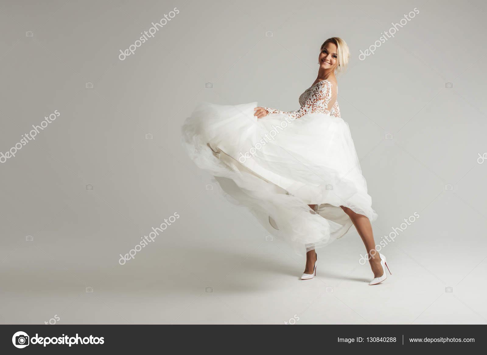 3d51fda12d52 Vackra attraktiv brud i brudklänning med lång hel kjol, vit bakgrund,  dansar och ler