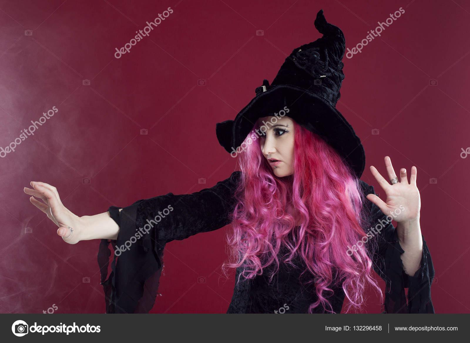 Donna attraente in cappello di streghe e costume con capelli rossi esegue  magia su uno sfondo rosa. Halloween fd97d046a97f
