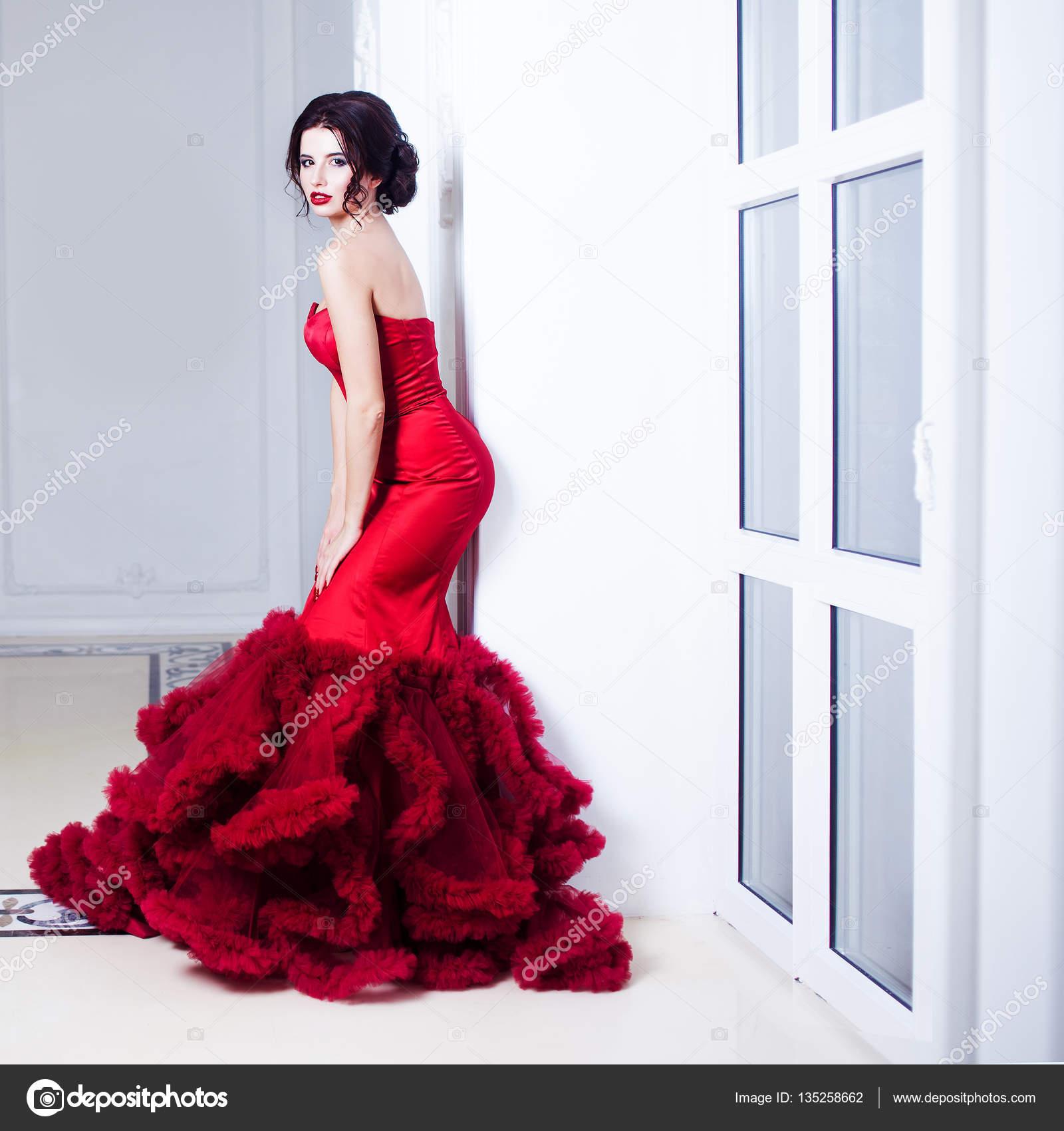 7cd7e272278 Robe de beauté Brunette modèle femme en rouge de la soirée. Belle mode luxe  maquillage et coiffure. Silhouette séduisante. Une jeune fille se tient  près du ...