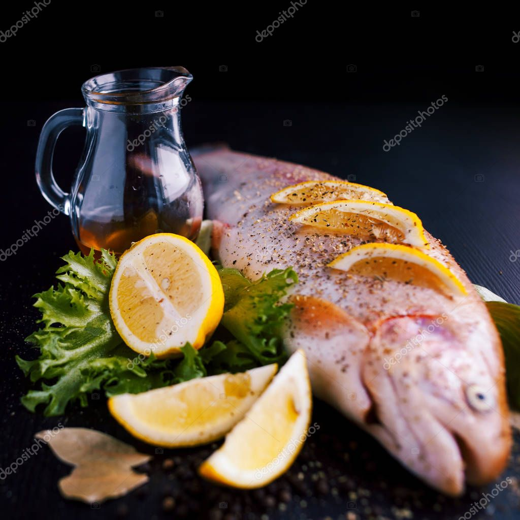 Fresh trout and ingredients to prepare fish dishes on black table. Focus on the decanter of olive oil