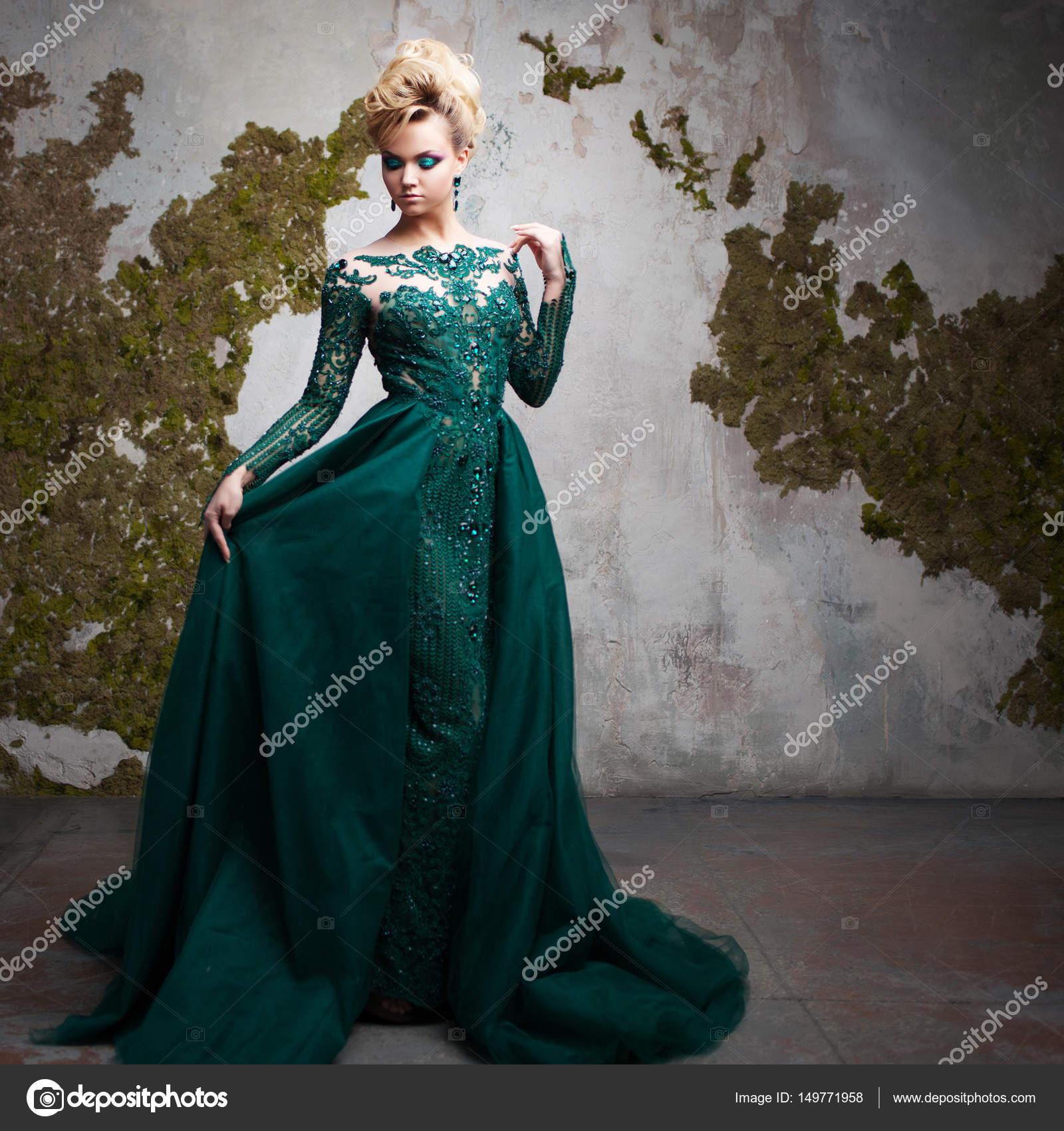 531c77fabf0 Portrait de jeune femme blonde séduisante dans une magnifique robe verte.  Fond texturé