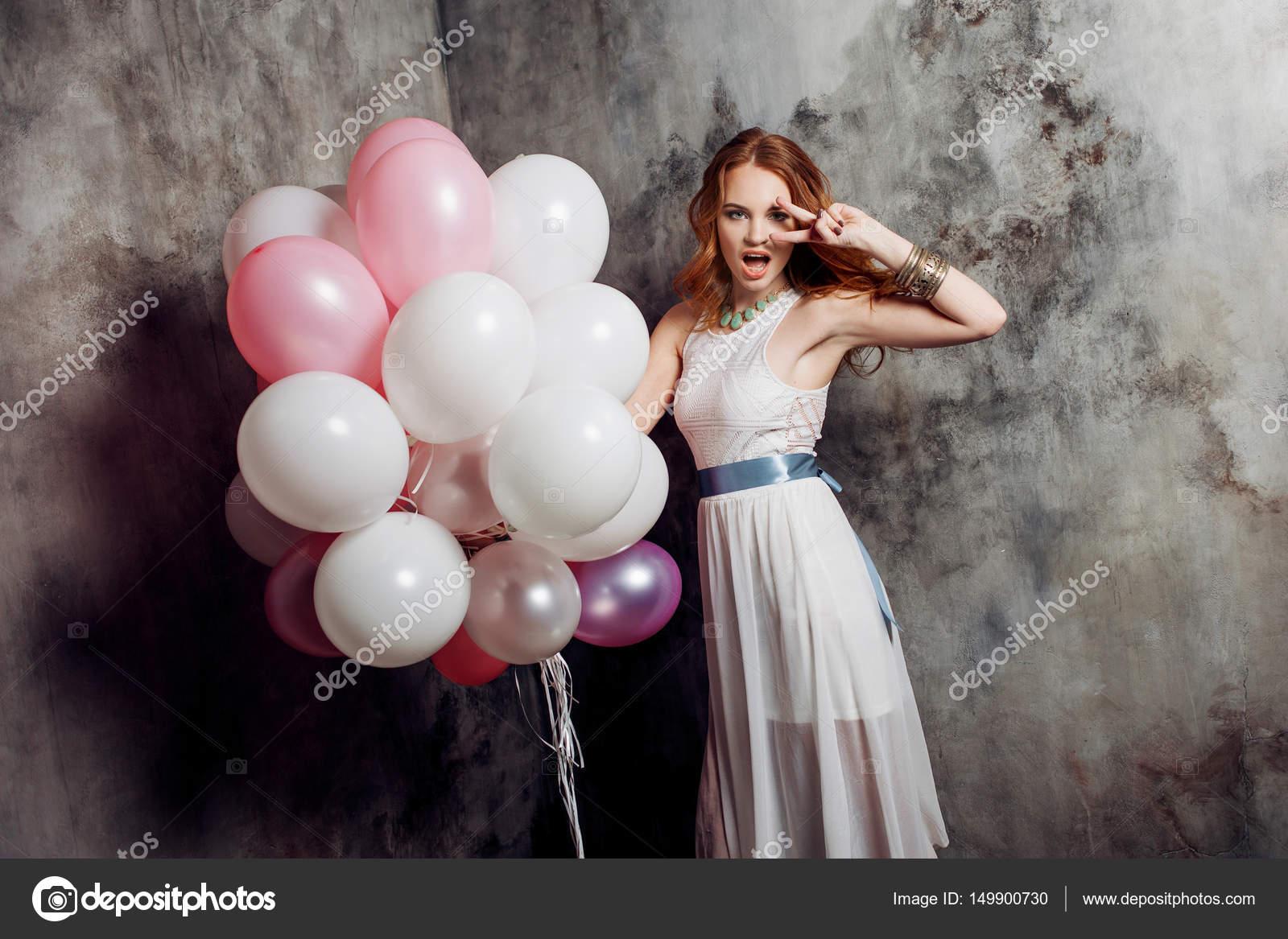 Rothaarige Schönheit junge Frau in einem weißen Kleid hält ein ...