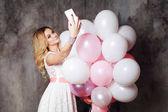 Okouzlující mladá blondýnka v bílých šatech, držící velký ranec balónků. Šťastné a veselé děvče dělá selfie.