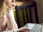 Mladá blond žena používá notebook, sedí doma. Koncepce práce v Internetu