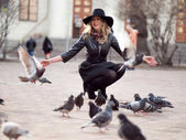 Fotografie Young girl in a stylish hat, in the street playing with a large number of pigeons. Birds fly up