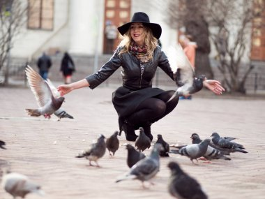 Young girl in a stylish hat, in the street playing with a large number of pigeons. Birds fly up