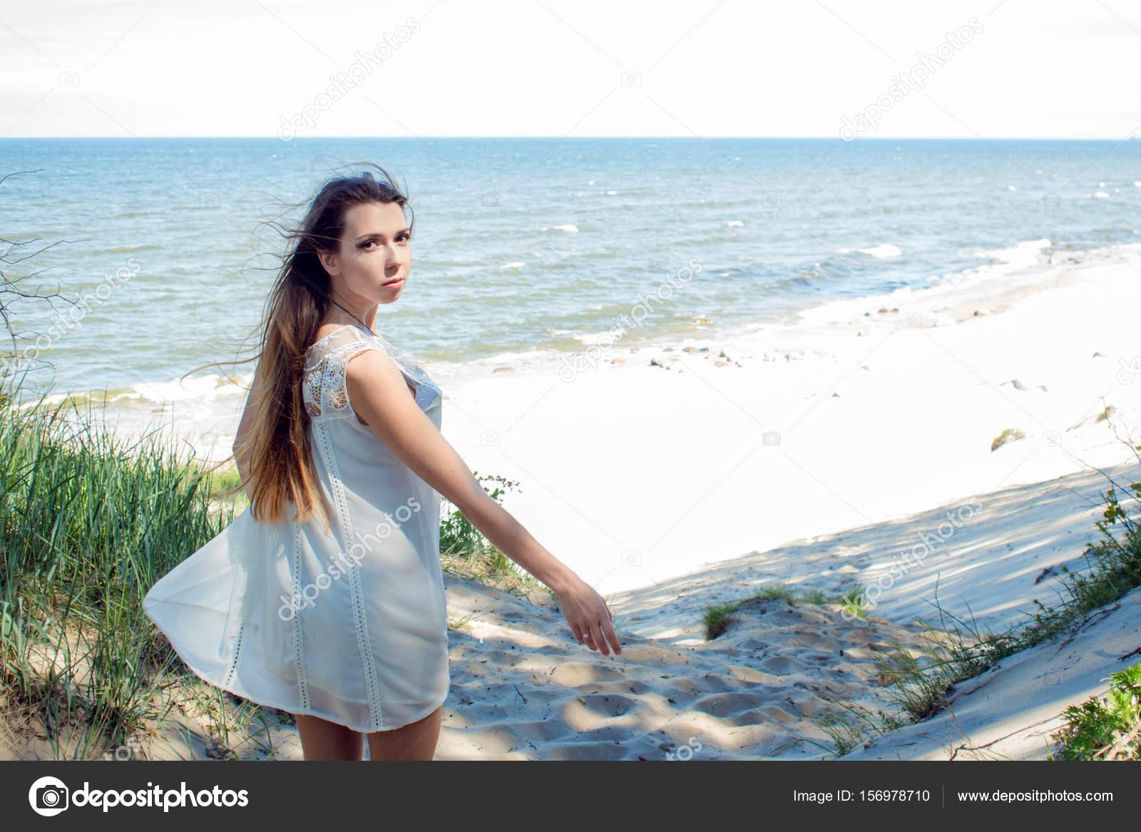 31d4cf8e2d57 Mladá půvabná brunetka žena na pobřeží moře. Krásná dívka v krátké bílé  letní šaty —