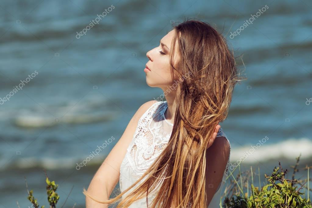 Young charming brunette woman on sea coast. Amazing view from the top. Portrait of young woman against clear sky