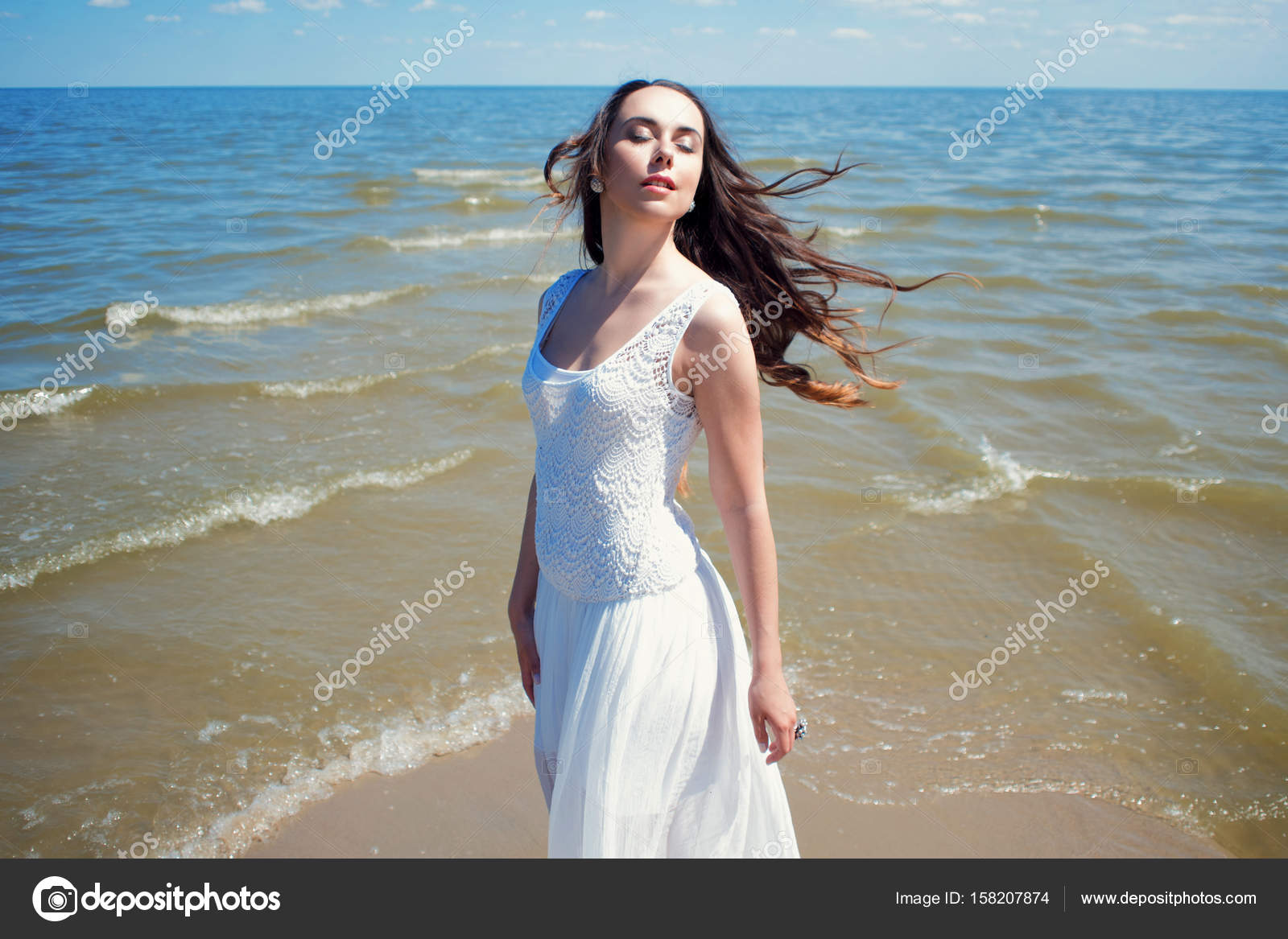8307ab5737ec Giovane bella donna castana in vestito bianco in riva al mare — Foto Stock