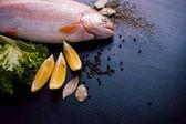 Čerstvý pstruh a ingredience na přípravu ryb jídla na černý stůl