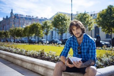 Guy in the blue shirt reading a book. Portrait of young handsome stylish man on the street.