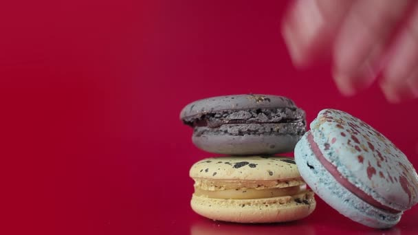 Macaron. Desserts on a bright raspberry background. Female hand puts cakes pyramid