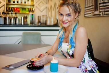Trendy girl with bright colored hair, sitting in cafe, drink coffee and eat dessert