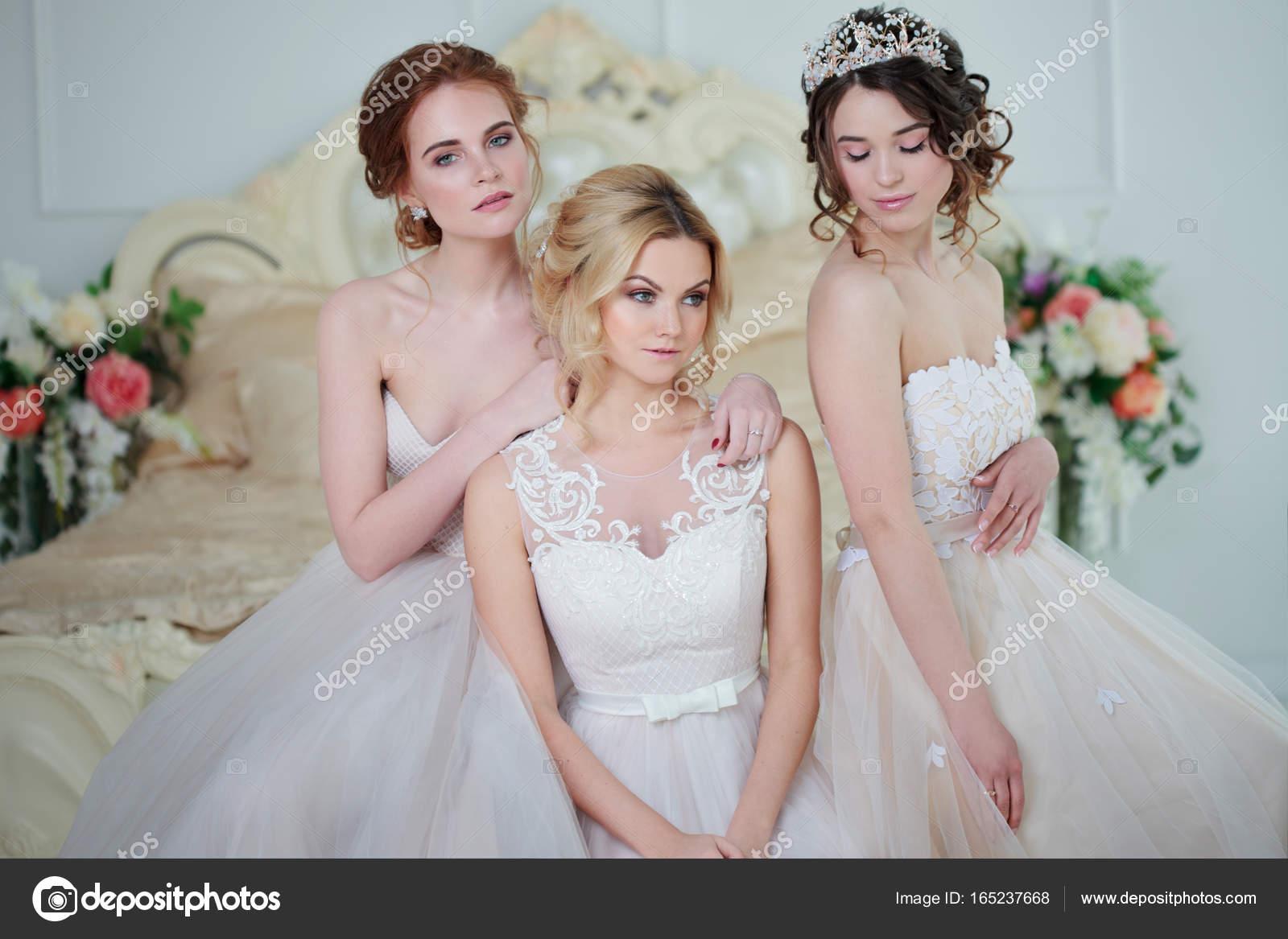 2e4210ba6311 Τρία κορίτσια σε Νυφικά φορέματα. Όμορφα λεπτή κορίτσια στο νυφικό σαλόνι — Φωτογραφία  Αρχείου
