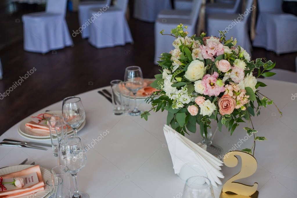 The numbering of the tables. Flowers in the restaurant, table setting