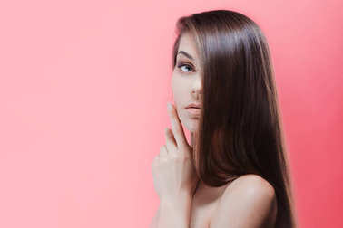 Stunning young brunette with perfect hair, on a pink background. Hair care