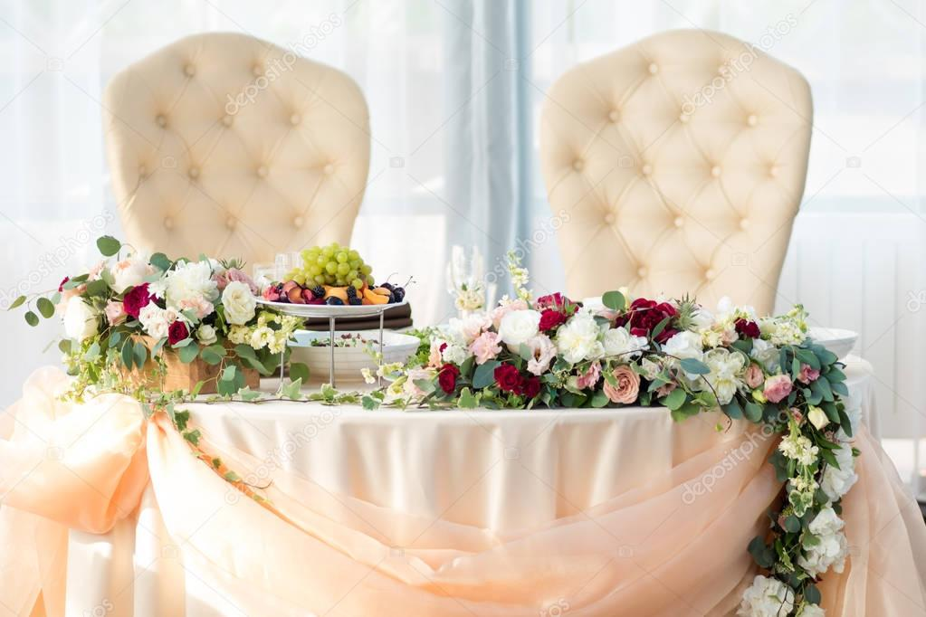 Table of the bride and groom in the restaurant. Wedding decor, flowers