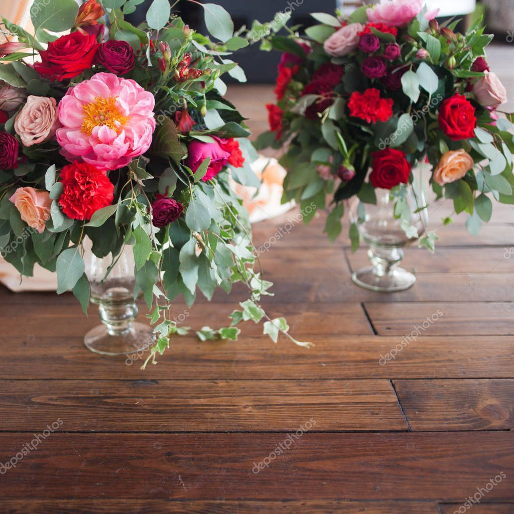 Vases with bouquets of red flowers on the floor. Wooden background