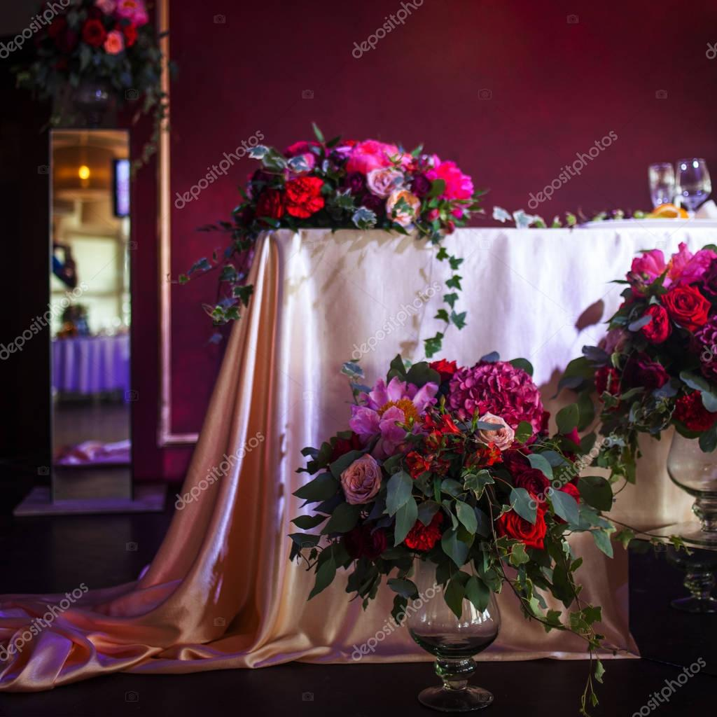 decor of the newlyweds. Silk tablecloths, red flowers
