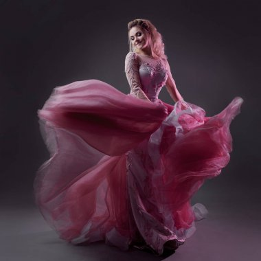 Glamorous lady in a chic pink dress with a train. Studio portrait on gray background