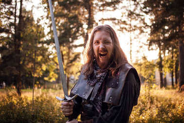 Battle. Knight in the forest. A guy in medieval costume with a sword