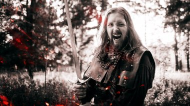 Battle cry, battle. Knight in the forest. Guy in medieval costume with sword. effect of fire and toning