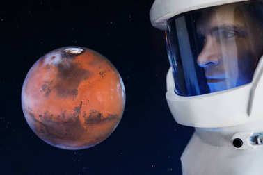 Development of Mars, concept. Astronaut, looking at the planet Mars. Elements of this image furnished by NASA.