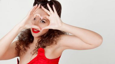 Charming lady in red corset, shows sign heart