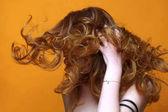Gyönyörű vörös hajú lány, luxus, göndör haj. Stúdió portré sárga háttéren. Kiváló haj
