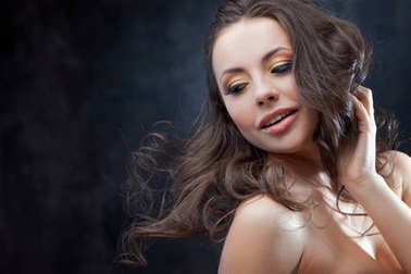 Brunette girl with long wavy hair . Beautiful model with curly hairstyle