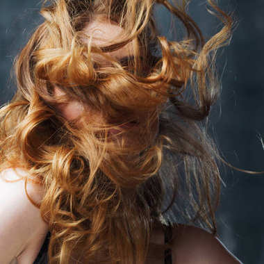 Excellent curly hair. Happy beautiful redheaded girl. Studio portrait on textured background. Flying long hair