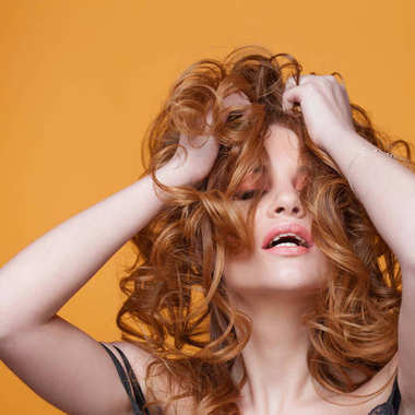 Happy redheaded young woman with luxurious curly hair. Studio portrait on yellow background. Excellent hair