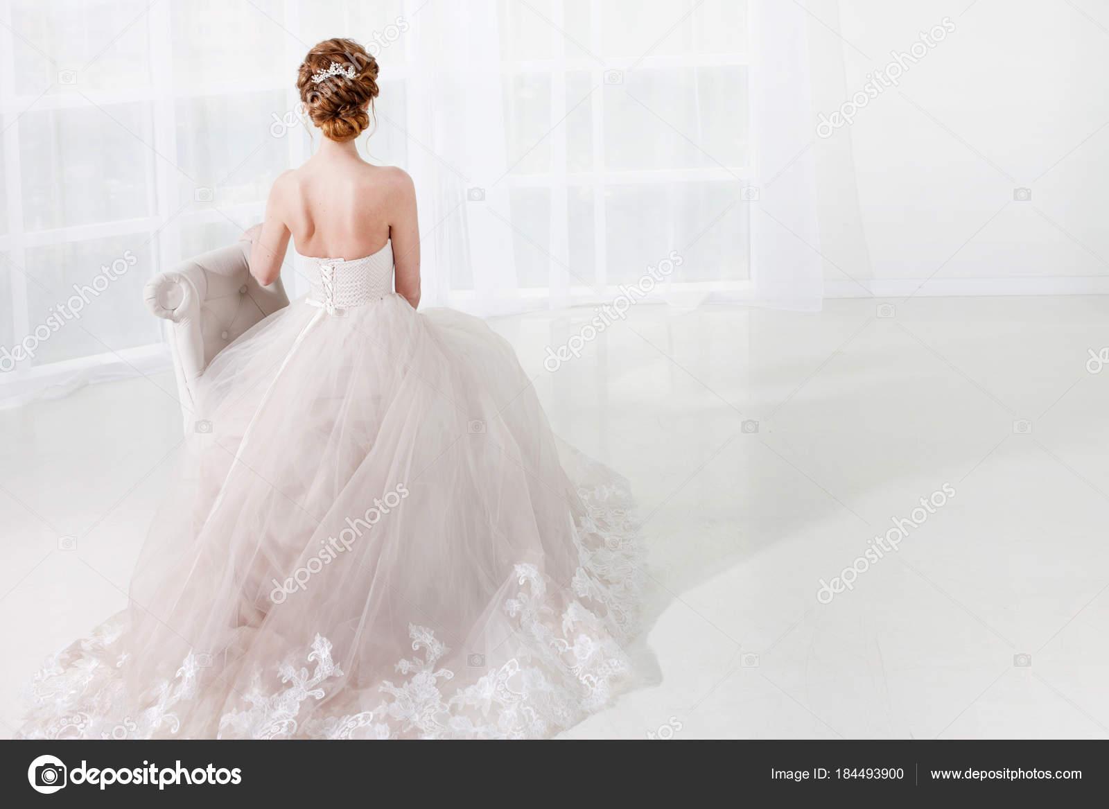 Schöne rothaarige Braut sitzt auf dem Stuhl, stilvolle Frisur wieder ...
