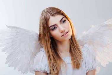 An angel from heaven. Young, wonderful blonde girl in the image of an angel with white wings. Portrait close-up