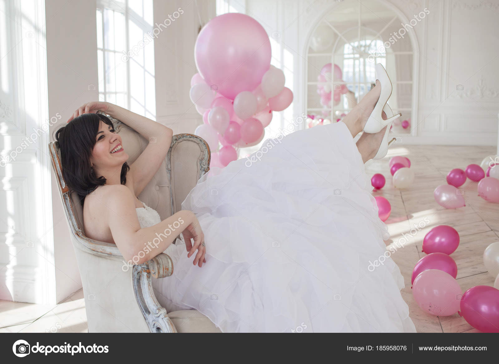 Young woman in wedding dress in luxury interior with a mass of pink ...